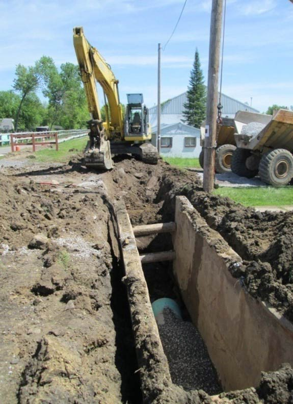 heavy equipment digging up sewer pipe for replacement